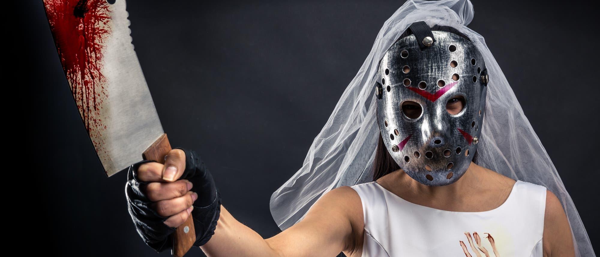 Braut mit Eishockeymaske und blutigem Hackmesser in der Hand
