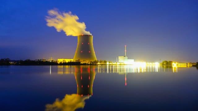 Kühlturm mit Dampfwolke und hell erleuchtete Kraftwerksgebäude in der Dämmerung, fotografiert vom gegenüberliegenden Flussufer.