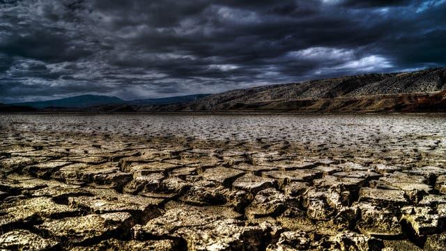 Endzeitkitsch-Landschaft mit Trockenrissen im Vordergrund, dunklen Hügeln im Hintergrund und ominösen Wolken.