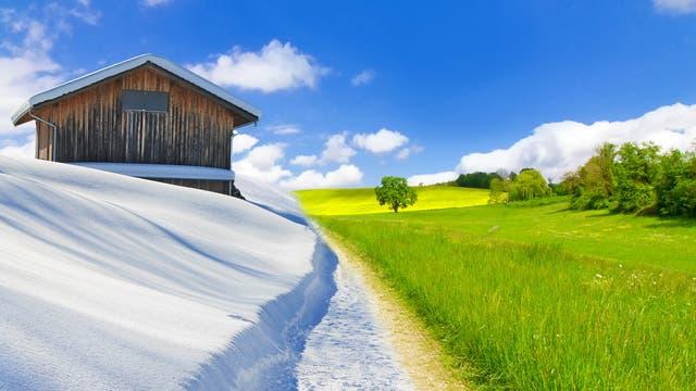 Links eine schneebedeckte Landschaft, rechts grüne Wiese und Wald.