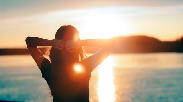 Frau genießt Sonnenuntergang am See