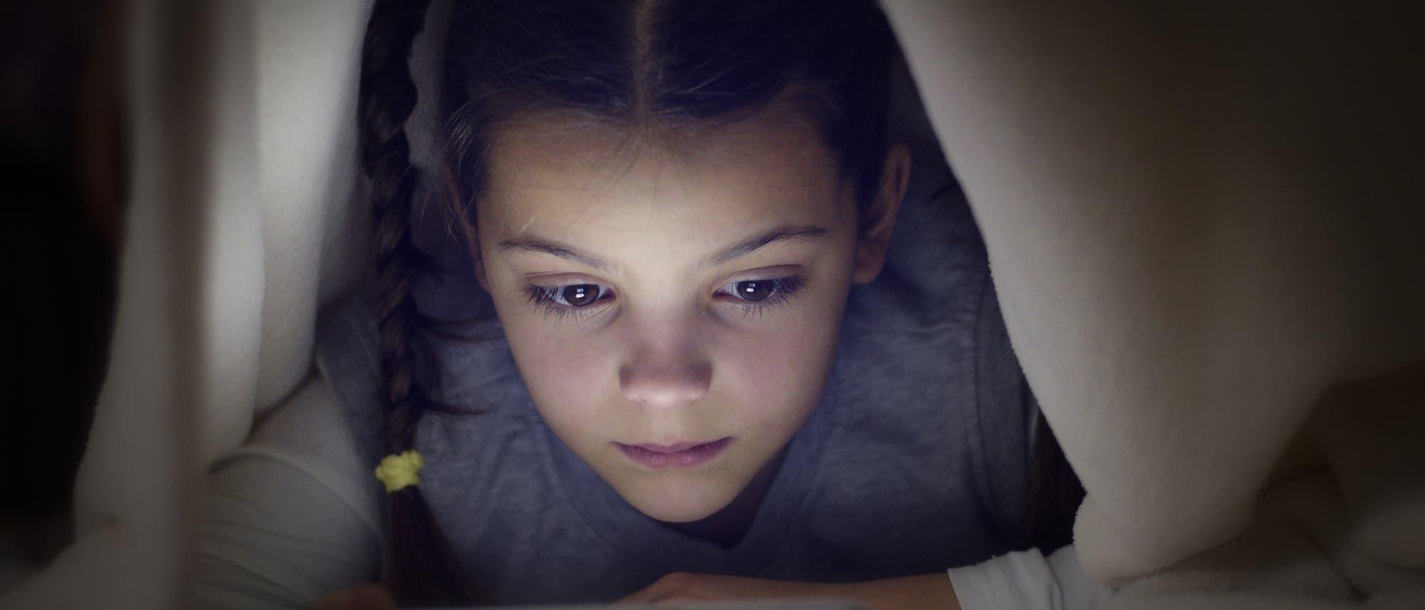 Ein junges Mädchen liegt unter einer Bettdecke und guckt konzentriert auf ein Bildschirmgerät.