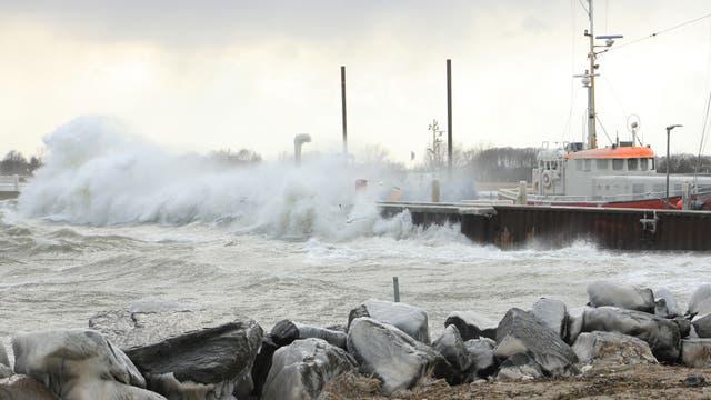 Eine Welle bricht sich an einer Hafenmole, hinter der ein Schiff liegt.