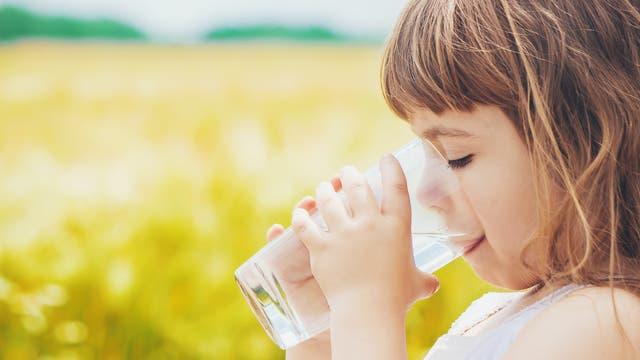 Ein Mädchen trinkt Wasser aus einem Glas. Im Hintergrund unscharf ein Rapsfeld.