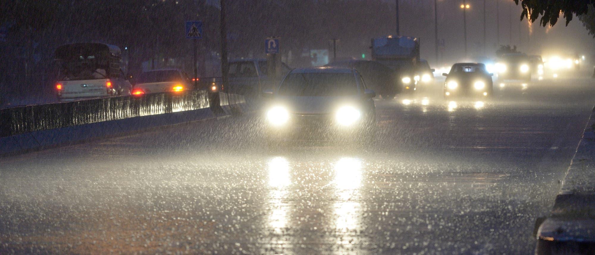 Autos auf regennasser Fahrbahn bei Nacht.