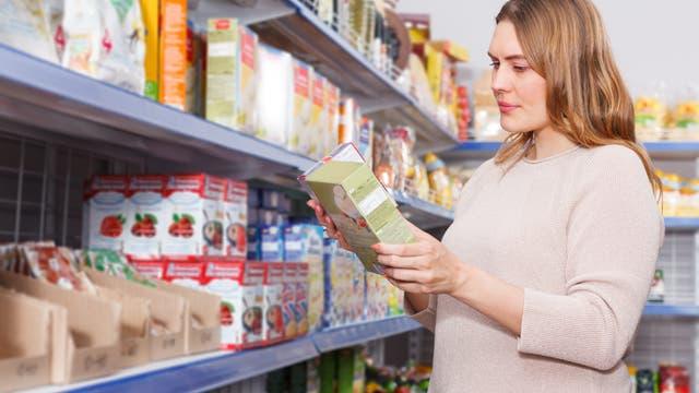 Eine Frau steht vor einem Supermarktregal und betrachtet einen Karton. Die meisten Menschen möchten angeblich wissen, was in ihren Lebensmitteln drin ist. Aber wenn man es ihnen erzählt, schmollen sie rum und sagen, dass sie in Chemie ja noch nie gut waren.