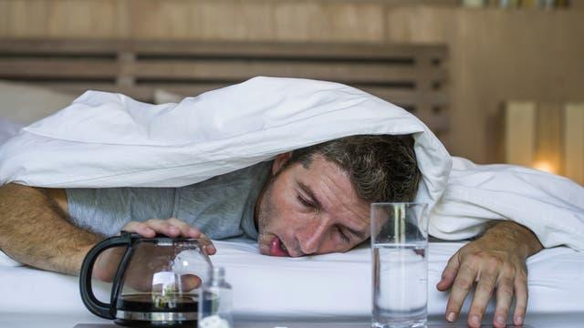 Ein verkaterter Mann guckt unter einer Bettdecke hervor.