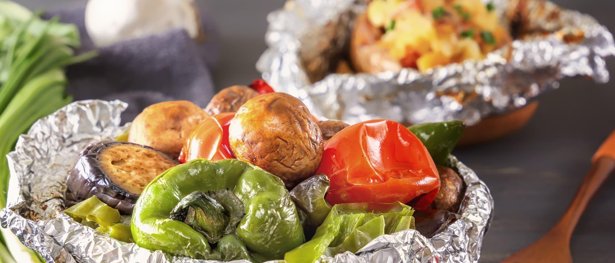 Im Vordergrund gebackenes Gemüse in einer Schüssel aus Alufolie, hinten eine halb ausgewickelte Backkartoffel.