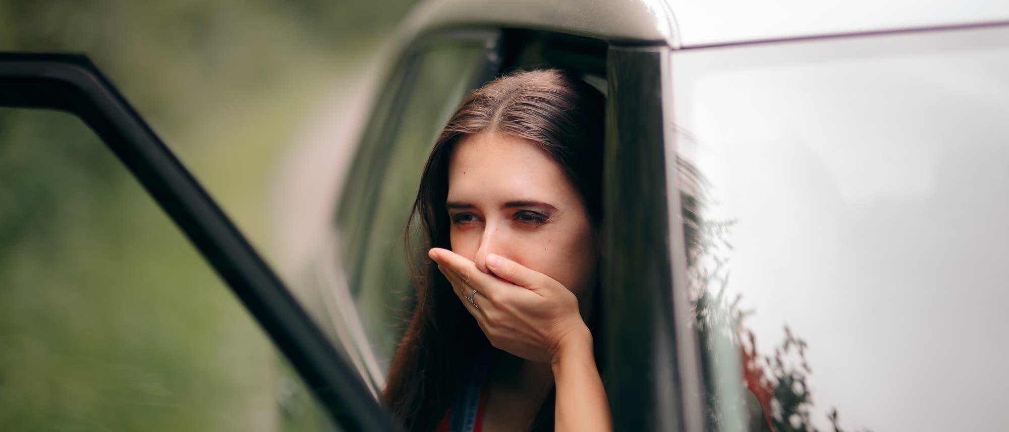 Frau, der bei der Autofahrt schlecht geworden ist.