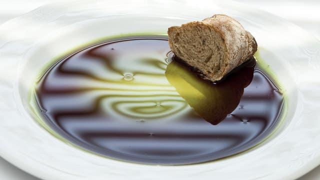 Ein dunkles, grünliches Öl auf einem Teller. Daneben ein Stück Brot.