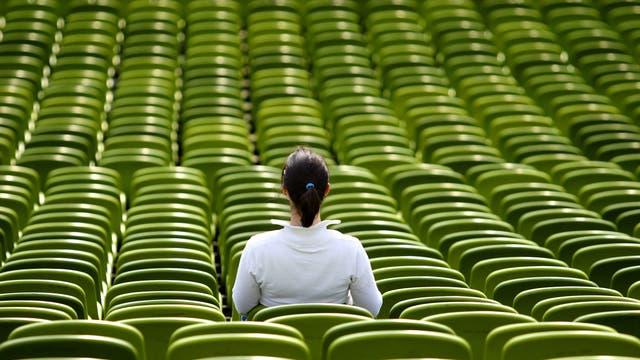 Eine Frau, von hinten fotografiert, allein zwischen unbesetzten Plastikstühlen.