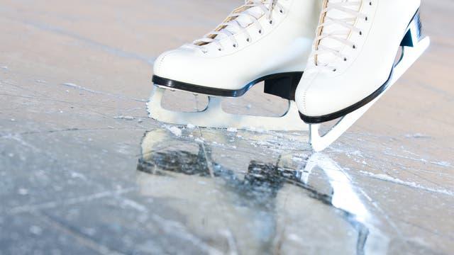 Zwei Schlittschuhe - mutmaßlich mit einer Person darin - auf einer geringfügig zerkratzten Eisoberfläche.
