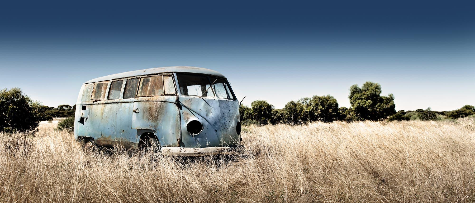 Ein verlassener Campingbus steht in der Landschaft herum.