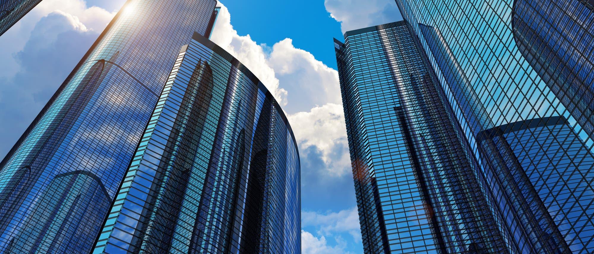 Mehrere Hochhäuser mit Glasfassaden vor blauem Himmel.