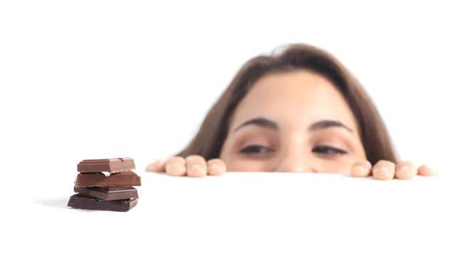 Frau schaut auf Schokolade