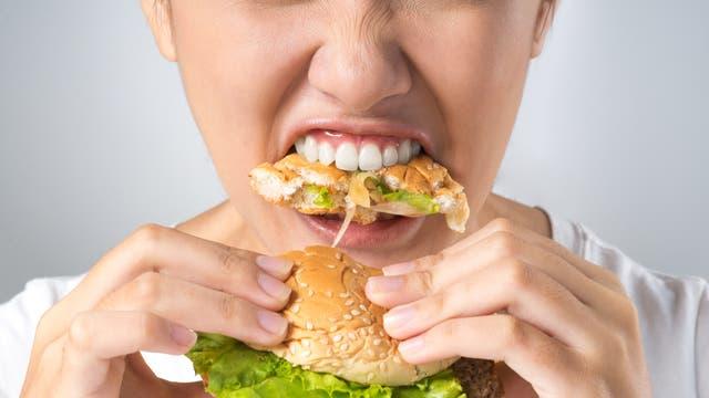 Frau beisst kräftig in einen Cheeseburger