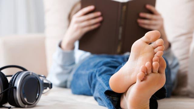 Frau liest ein Buch auf der Couch