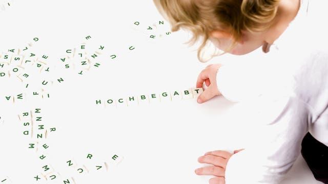 """Ein Kind legt das Wort """"hochbegabt"""" mit Scrabble-Steinchen. Tatsächlich hat es natürlich ein Erwachsener gelegt und dann auf den Auslöser gedrückt. Das Bild stellt also nicht die Eigenschaften des Kindes dar, sondern Wünsche und Erwartungen von Erwachsenen, passend zum Thema."""