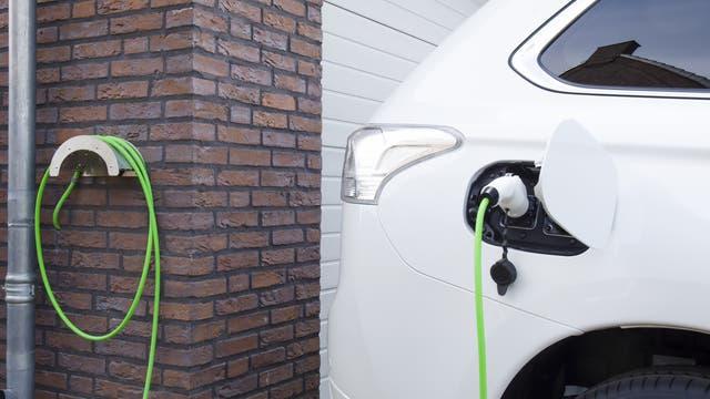 Ein E-Auto hängt zu Hause am Stromnetz