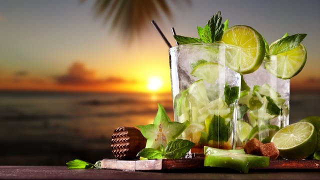 Zwei Mojitos auf einem Tisch vor der über dem Meer untergehenden Südseesonne. Leider scheinen die Drinks ohne Angostura gemixt zu sein und enthalten deutlich zu viel Limette im Vergleich zur Minze. Insofern ist das eher ein verunfallter Caipi.