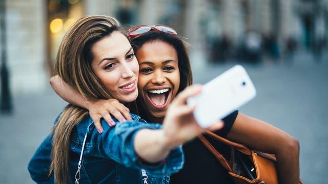 Zwei junge Frauen machen ein Selfie an einem öffentlichen Ort.