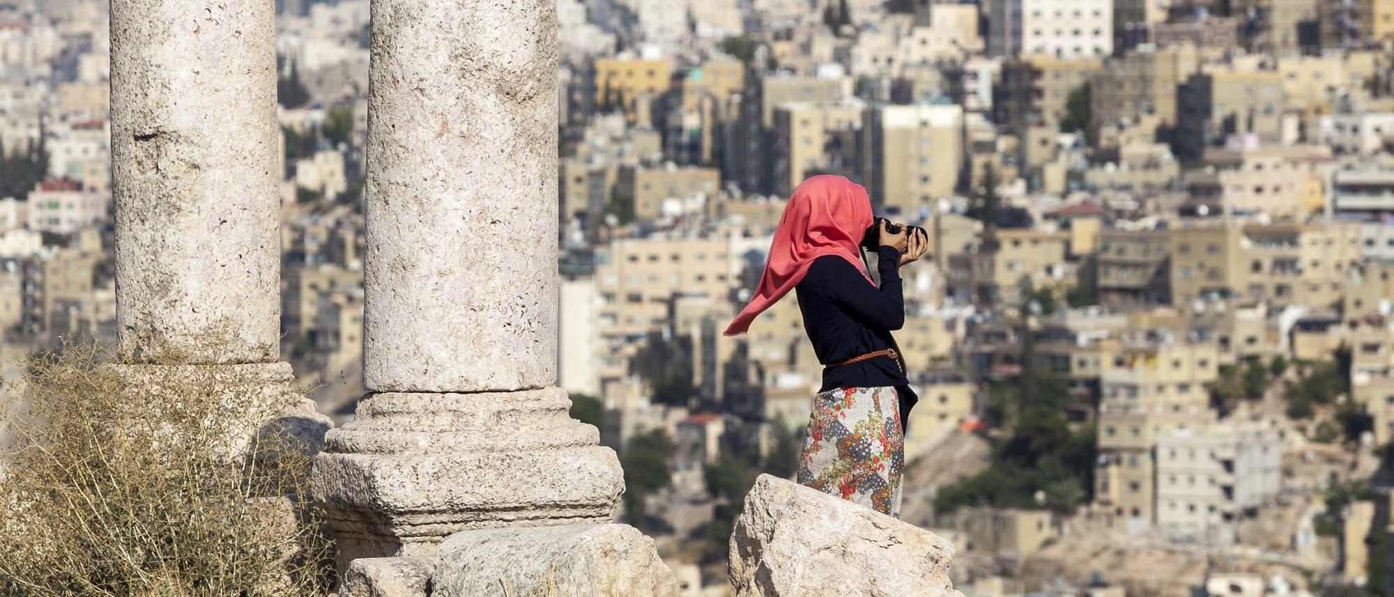 Eine junge Frau mit rotem Kopftuch steht mit einer Kamera filmend neben zwei römischen Säulenstümpfen vor den Häusern von Amman