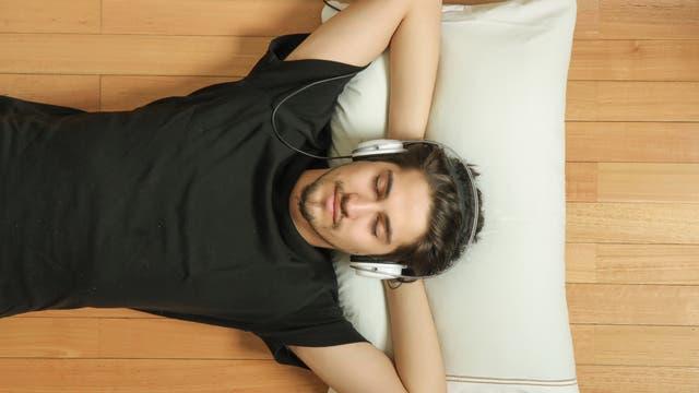 Mann mit Kopfhörer liegt entspannt mit geschlossenen Augen