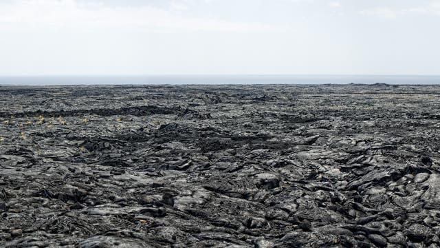 Flaches Lavafeld erstreckt sich zum Horizont, dahinter Meer und dunstiger Himmel