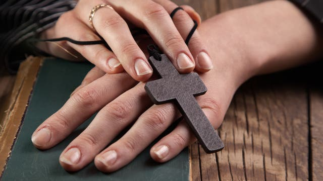 Zwei Hände halten einen hölzernen Kreuzanhänger.