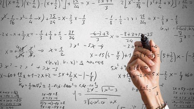 Eine Person schreibt Gleichungen auf eine Glasscheibe. Interessant daran ist, dass sie anscheinend die ganze Zeit in Spiegelschrift schreibt.