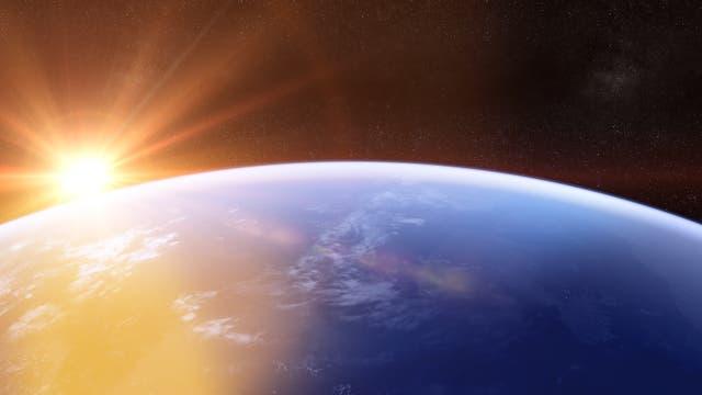 Sonnenaufgang aus dem All über dem vom Ozean eingenommenen Horizont.