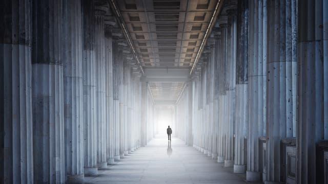 Eine sehr kleine menschliche Figur in einem sehr imposanten Säulengang. Symbolbild für Einsamkeit in der Wissenschaft oder gescheiterte Architektur.