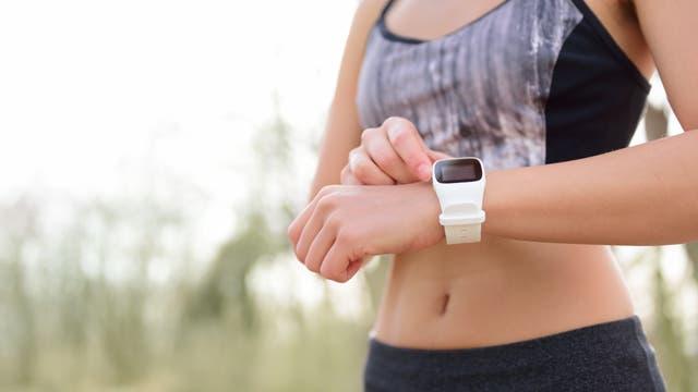 Torso einer sportlich gekleideten Frau, im Vordergrund Arm mit Smartwatch am Handgelenk. (der Körper ist vermutlich vollständig und unbeschädigt, der Rest ist nur außerhalb des Bildausschnitts)