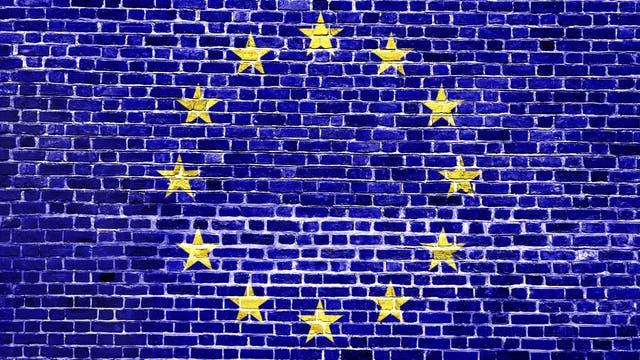 Die EU-Flagge auf einer Backsteinmauer. Oder wie man auf der anderen Seite des Kanals liest: Mene mene tekel u-parsin.