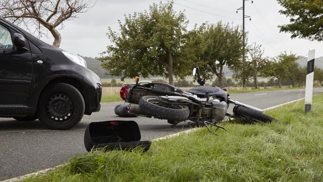 Ein Motorrad liegt vor der Front eines Autos. Das ist natürlich nur ein Symbolbild. Bei einem echten Unfall fliegt das Motorrad viel, viel weiter.