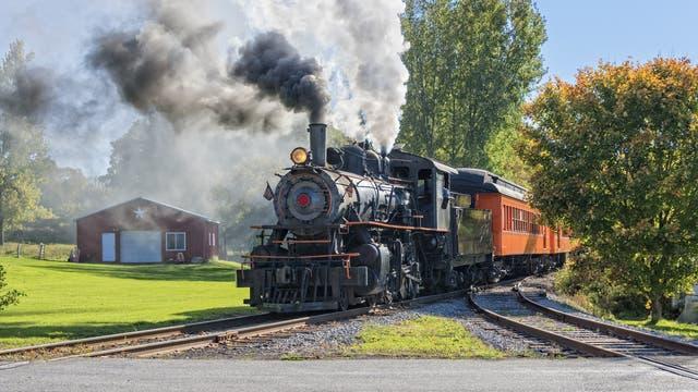 Eine alte Dampflokomotive zieht einen Zug durch den ländlichen Raum.