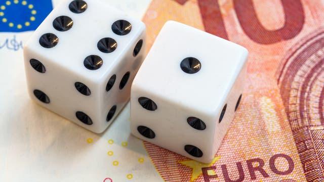 Zwei weiße Würfel liegen auf einem Zehn-Euro-Schein. Das ist wieder so eine Szene, die auf der ganzen Welt nie jemals irgendwo vorkommt außer in Symbolbildern aus Bilddatenbanken.