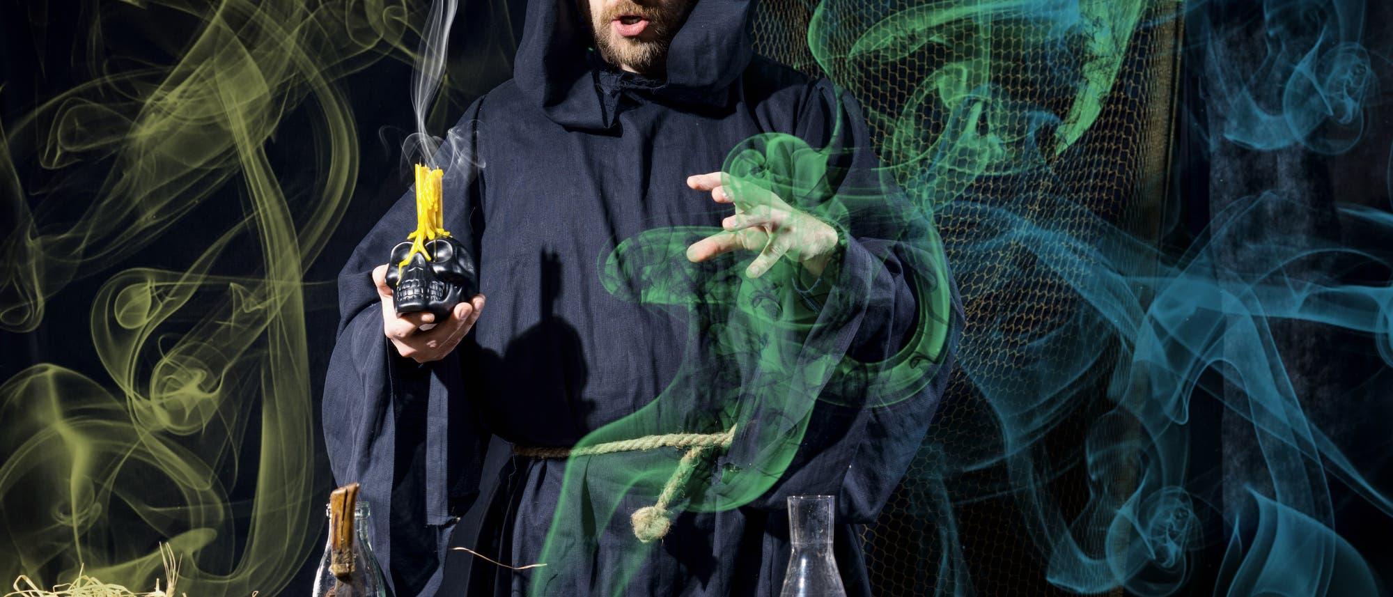 Ein Alchemist mit Kutte hält eine Kerze auf einem Totenschädel und forscht im bunten Dunst