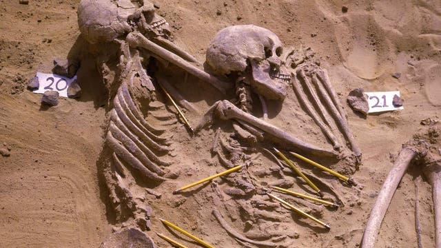 Zwei Tote vom Friedhof Jebel Sahaba. Wie für diese Zeit üblich, waren die Toten auf der Seite liegend bestattet worden. Die Bleistifte deuten auf Fundstellen von Steinprojektilen hin.