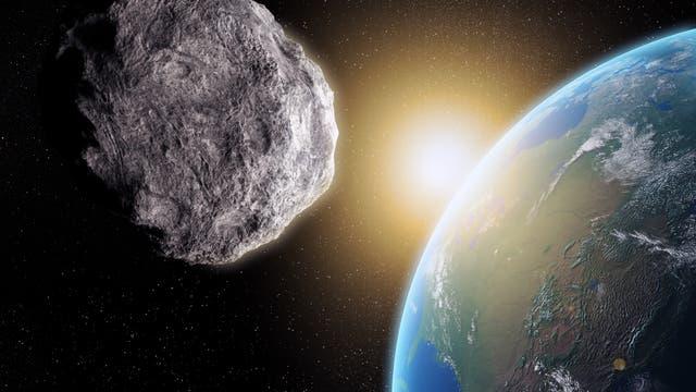 Ein Asteroid im Vordergrund fliegt auf die Erde zu. Wird er treffen? Viel spannender ist allerdings eine andere Frage: Wie kommt es eigentlich, dass die von Sonne und Erde abgewandte Seite des Asteroiden so exzellent ausgeleuchtet ist?