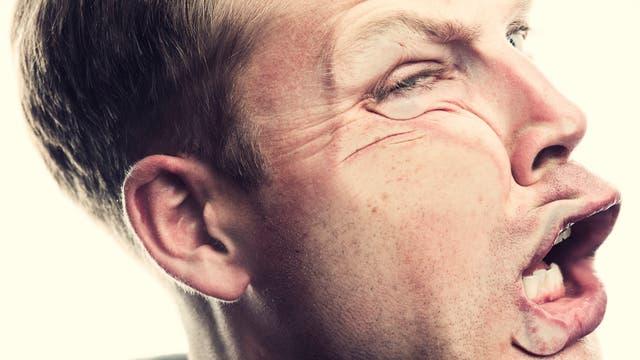 Ein Mann scheint gegen eine unsichtbare Wand zu laufen oder von einem unsichtbaren Objekt im Gesicht getroffen zu werden.