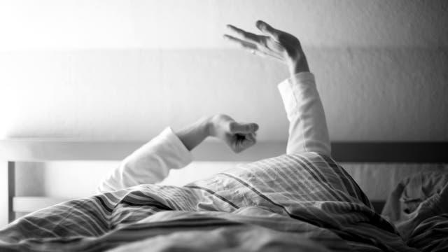 Ein Mann wacht auf und streckt sich.