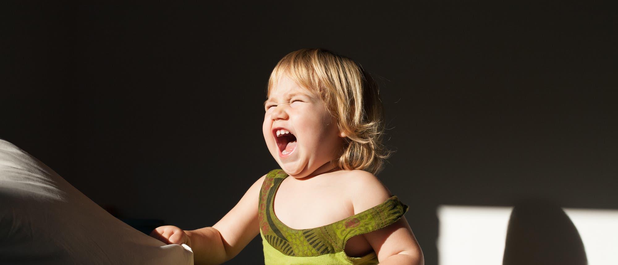 Ein fröhliches Kleinkind ruft die Sonne an