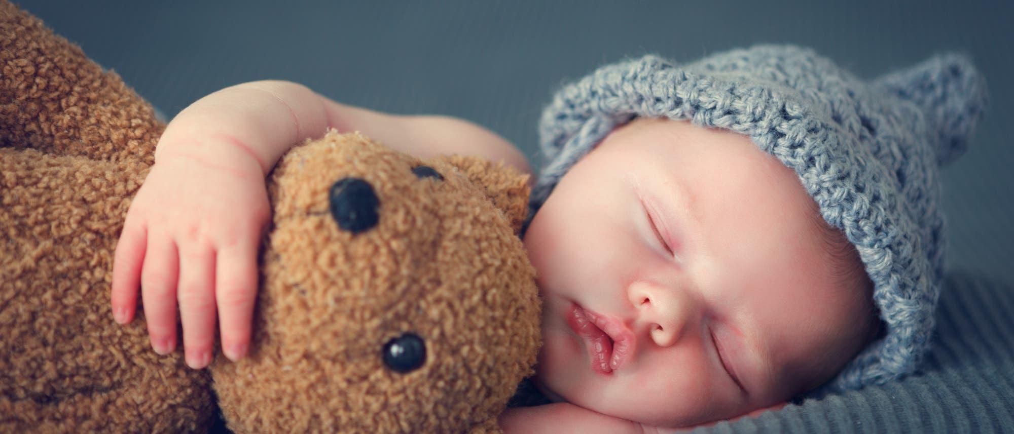 Schlafendes Baby mit Mütze und Stofftier
