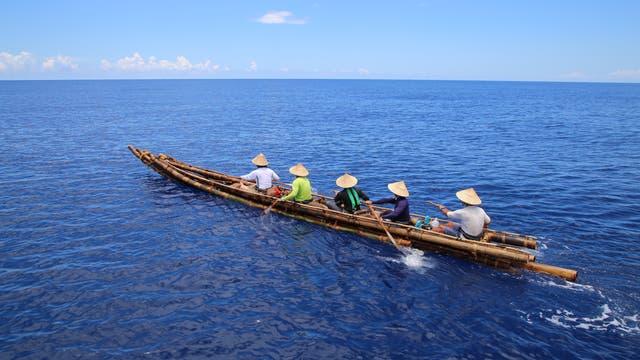Nachgebautes Bambus-Kanu mit fünf Ruderern