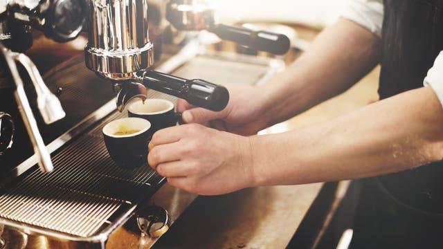 Zwei gefüllte Espressotassen unter der Düse einer Kaffeemaschine.