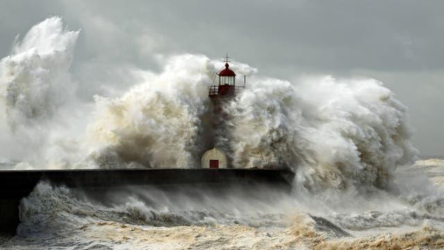 Gegen einen Leuchtturm peitschen Sturm und Wellen