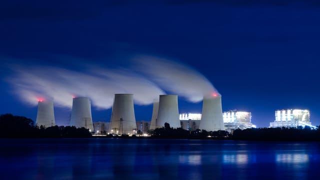 Hell erleuchtetes Braunkohlekraftwerk in der Nacht