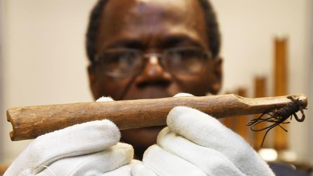 Der Wissenschaftler Ndzodo Awono zeigt im Schaumagazin des Bremer Überseemuseums eine Pfeife aus Kamerun