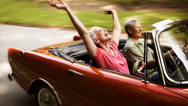 Ein glückliches älteres Paar fährt mit dem Cabrio in den Sonnenuntergang